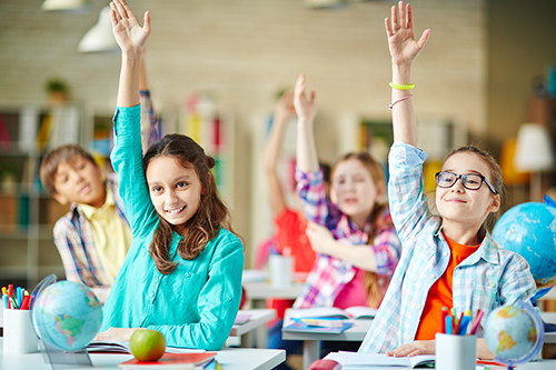 Intelligent group of school children raising their hands in to answer a question